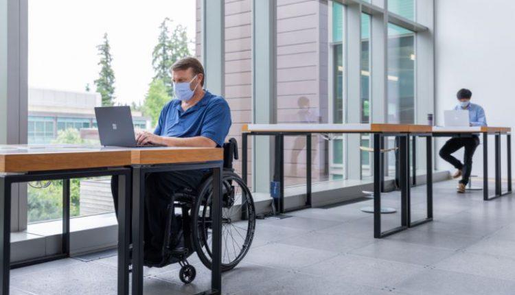 Hombre en silla de ruedas trabajando con un portátil.