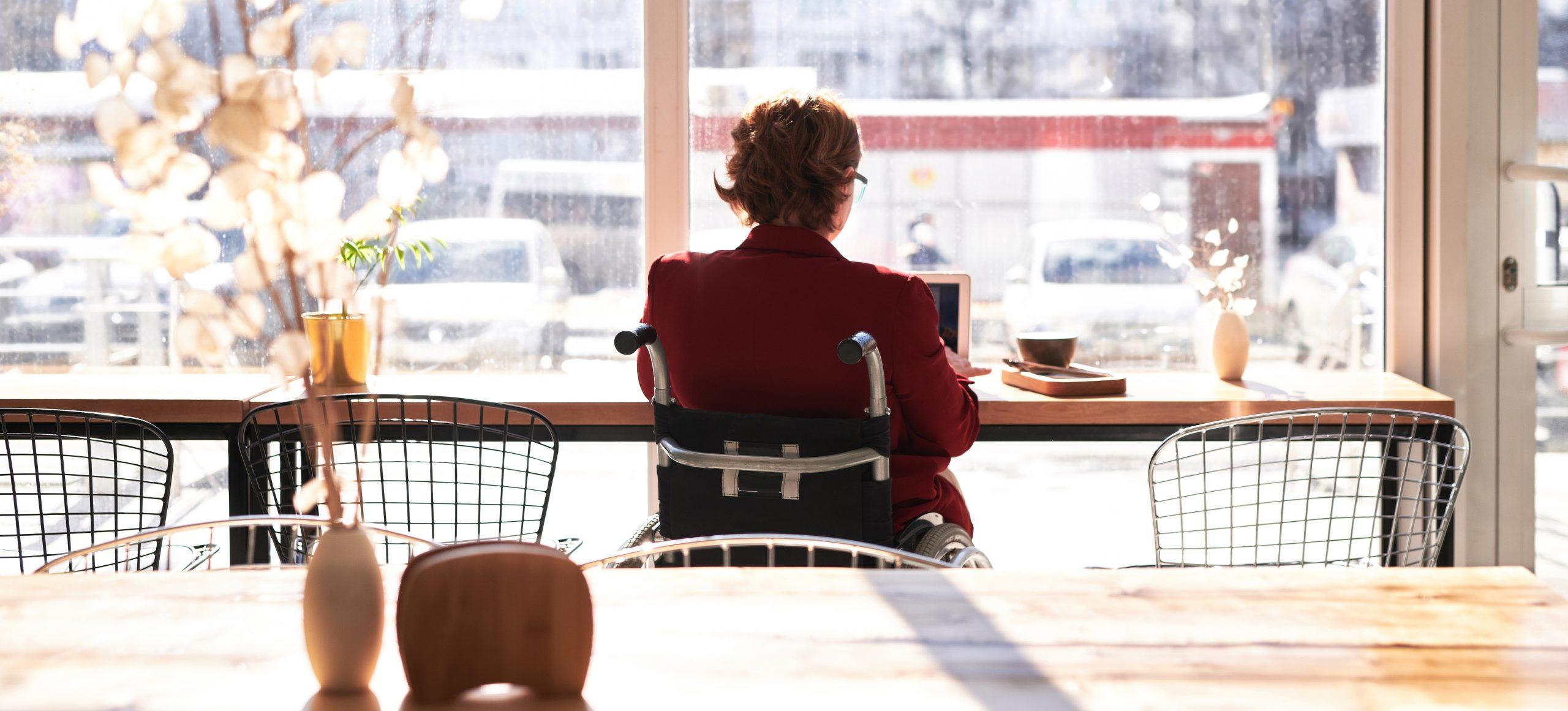 Mujer en silla de ruedas trabajando con un ordenador portátil.